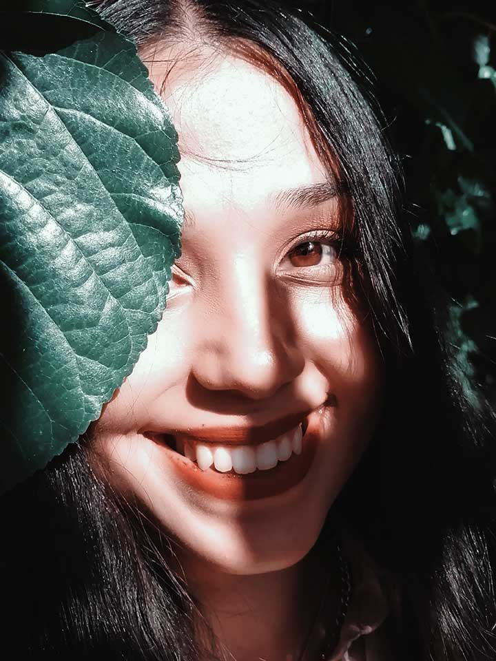 professional from an Asian country of origin smiles into the camera with a plant leaf in front of her face