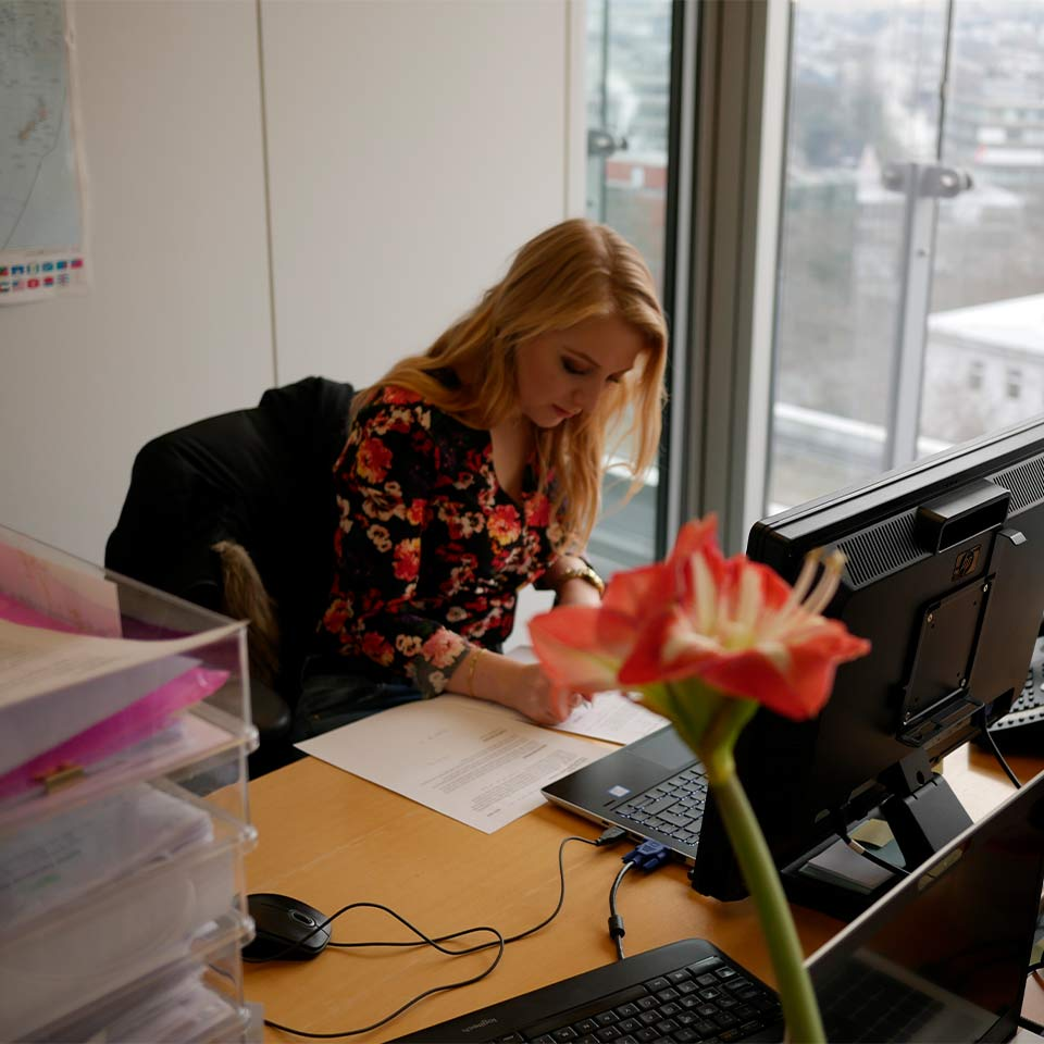 An international professional sitting at her desk in the office and filling out an application for her work in Germany