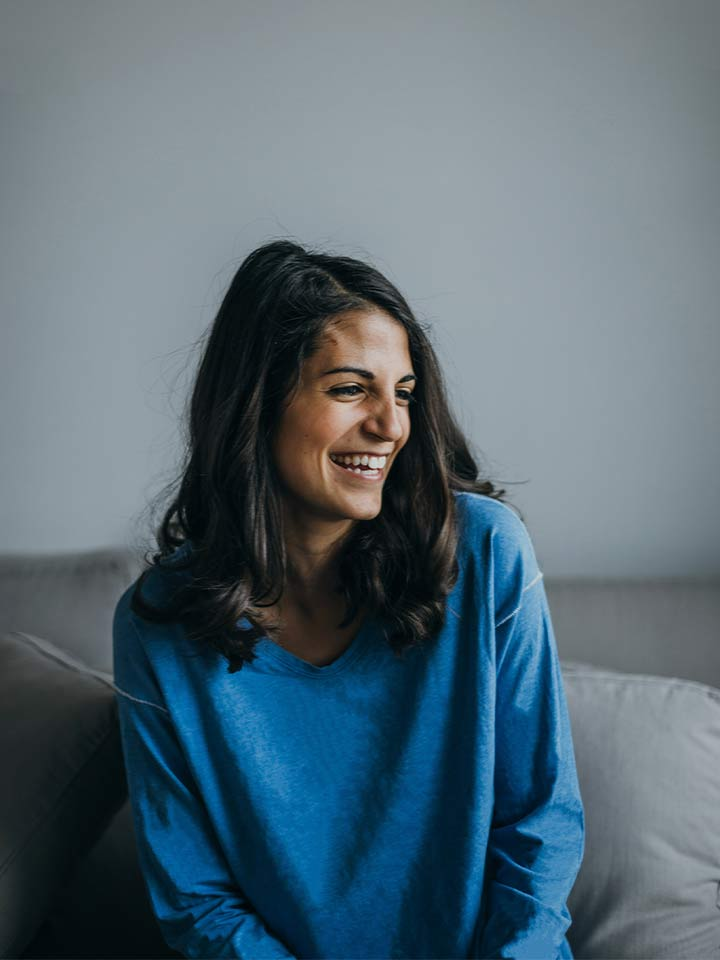 International professional with a blue jumper relaxing on a grey couch and laughing after her work